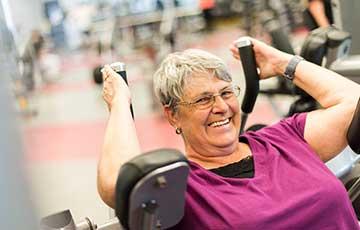 Senior woman using fitness equipment at the YMCA