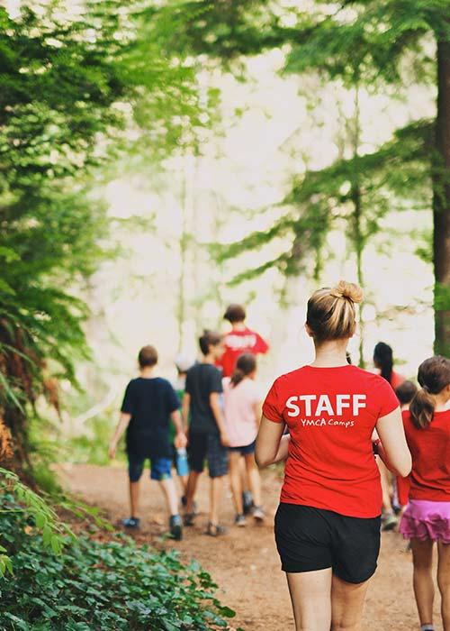 YMCA Camp Presqu'ile staff leading children through trail