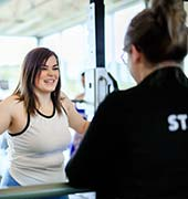 YMCA staff helping member with fitness program