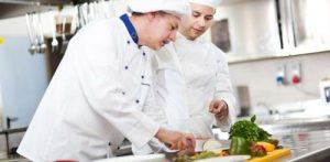 Chef and apprentice practising food safety