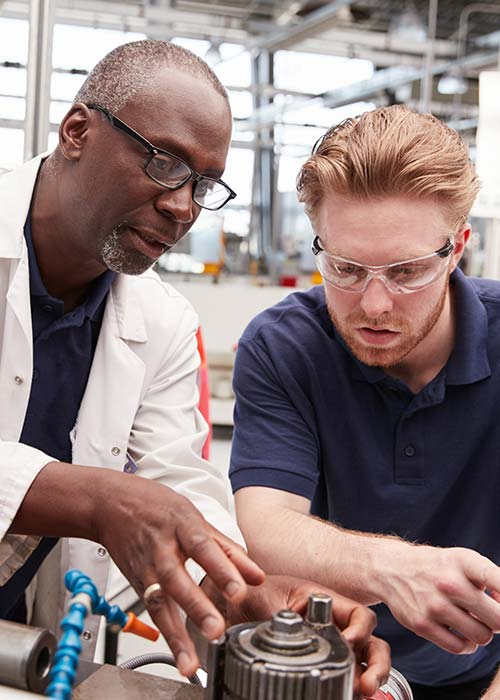 Older man with younger student working on mechanical project
