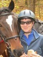 Susan Kuznicki, Manager of Finance, posing with horse