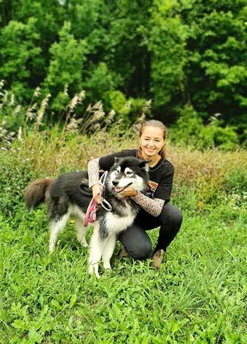 Young girl with arms around a Husky dog