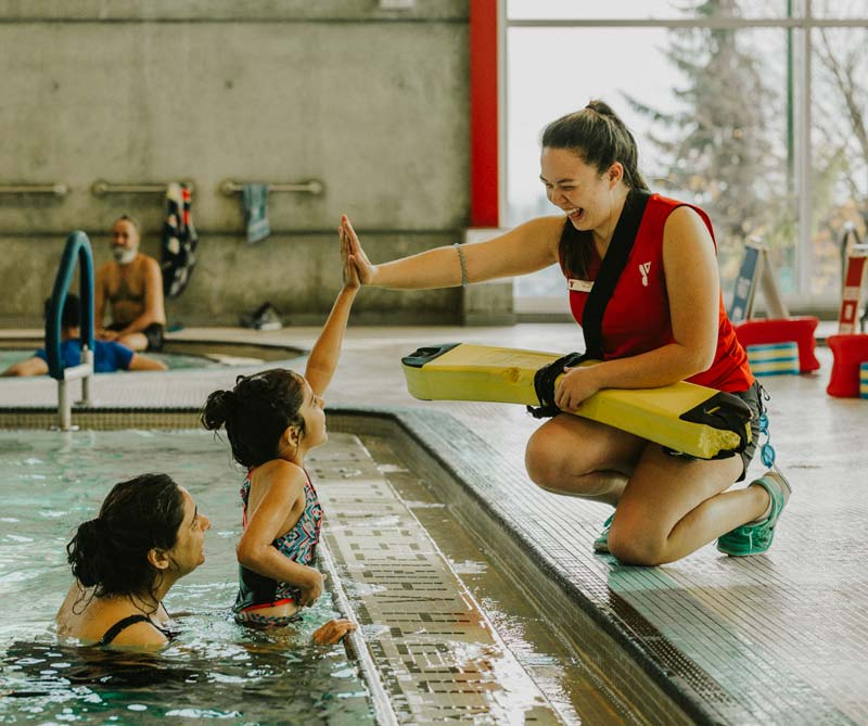YMCA lifeguard giving young swimmer a high five