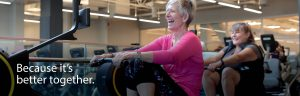Because it's better together. Two older woman using rowing machines.