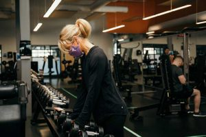 Woman with mask on using weights at the gym
